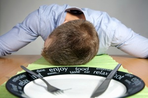Tired Man At Table With Plate - charlotte hormone imbalance treatment