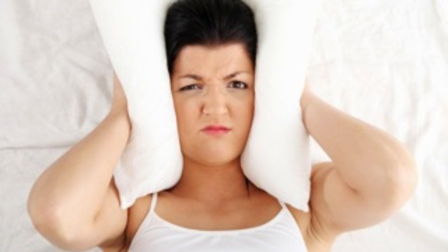 Woman Holding Head With Pillow - charlotte hormone imbalance treatment