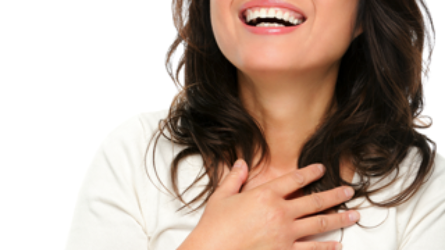 Happy Woman Holding Her Chest - autoimmune disorder treatment in charlotte