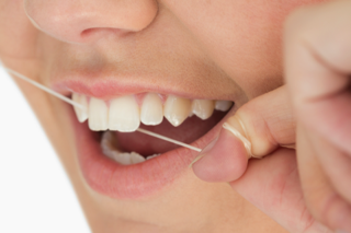 Woman Flossing Her Teeth - hormone imbalance treatment in charlotte