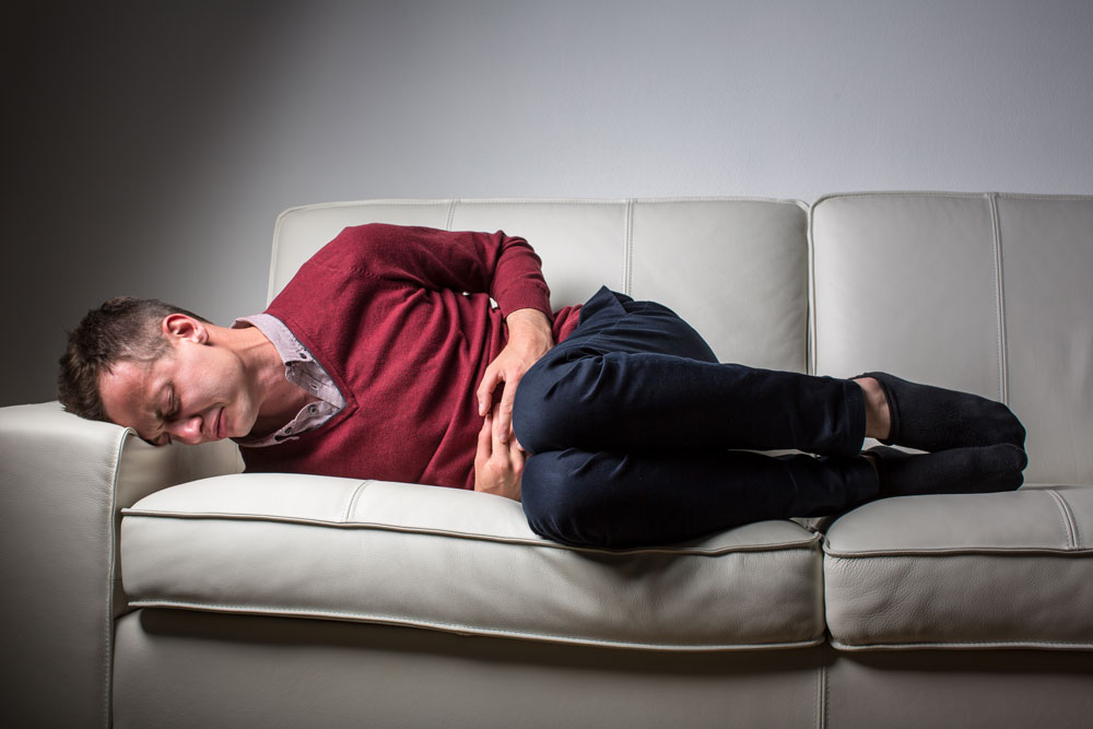 man-suffering-stomach-issues-on-couch