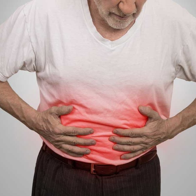 man affected by crohn's disease. he is in pain with hands on his stomach.